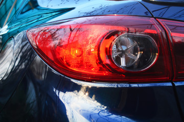 Red tail-light on a dark blue car.