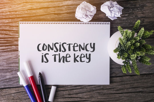 Consistency is the key word with Notepad and green plant on wooden background