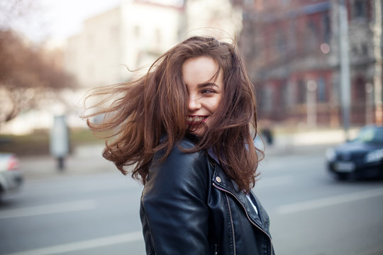 young beautiful brunette walking the city.leather jacket,urban backpack , bright red lips