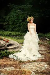 Fashionable bride with an artful look in a lush white dress is standing on a dark nature.