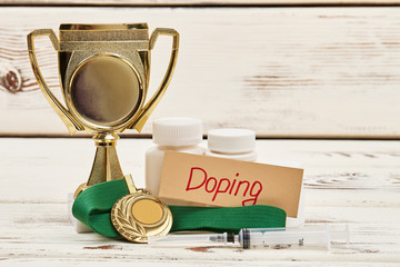 Cup, pills and medal. Reasons for sport disqualification.