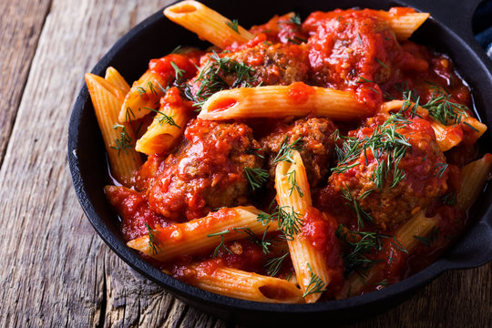 Meatball penne pasta with spicy tomato sauce and dill