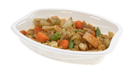 TV dinner of turkey breast with stuffing and vegetables isolated on a white background.