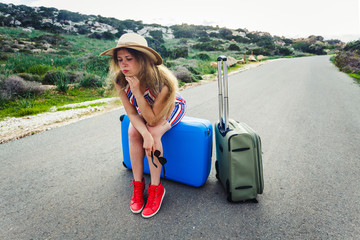 Stressed young tourist woman sitting on suitcases