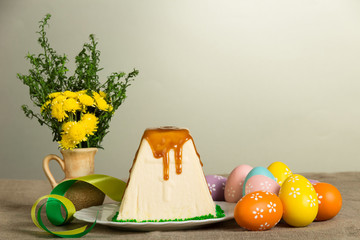 Traditional Easter curds dessert, easter eggs, flowers and ribbons on gray.
