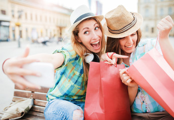 Shopping time. Beautiful smiling girls taking a selfie after good shopping. Consumerism, fashion, lifestyle concept