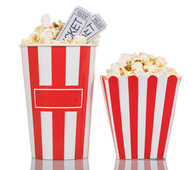 Two large striped boxes filled with popcorn, movie tickets on white.