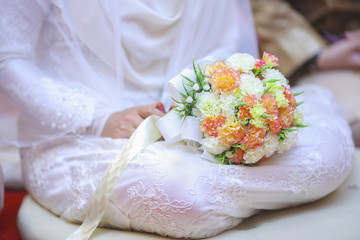 Bride with white dress holding a wedding flower.