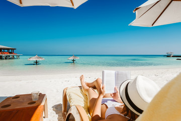 Wall Mural - Woman on sunbed reading book under parasol at tropical island
