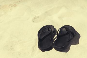 Beach shoes sandals flip-flops on sandy beach