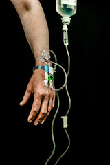 Hand and arm of patient with iv fluid treatment on black background, vertical.