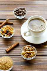 Cup of espresso black coffee on natural wooden background with healthy snacks - nuts and raisins
