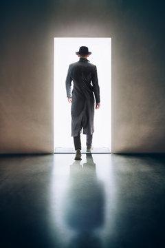 Man silhouette walking away in the light of opening door in dark room