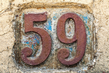 Old retro weathered cast iron plate with number 59