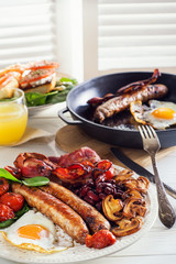 Delicious full English breakfast with  fried egg, bacon, sausage, tomatoes, beans and mushrooms. Traditional English breakfast.