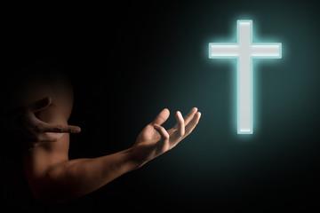 Man praying to luminous cross