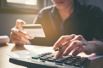 Saving money concept Man hand using calculator and holding credit card shopping online Row and coin stack growing business