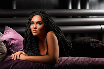 The girl is lying on the bed. Stylish hairstyle, dreadlocks. Black lady