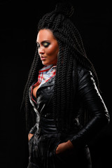 Girl in a leather jacket. Black background. Creative hairstyle, dreadlocks