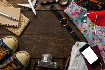 Top view accessories  travel with mobile phone,passport,camera,headphones,notepaper,sunglasses,watch on table wooden with copy space.Travel concept.