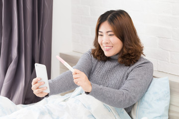 Happy asian woman holding pregnancy test and taking selfie by smartphone