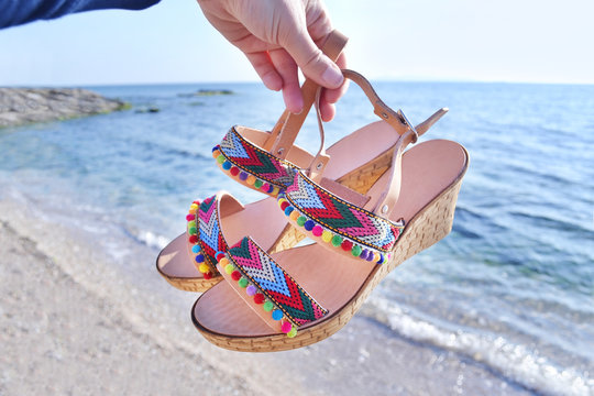 bohemian greek sandals on the beach - summer shoes advertisement