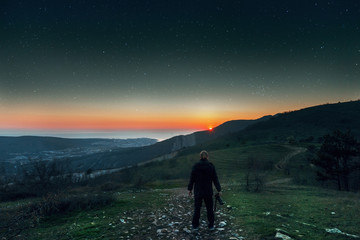 A young man stands on top of a mountain and enjoys the sunset and starry sky