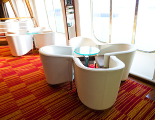 armchair and table close to a window for rest in a cruise ship.