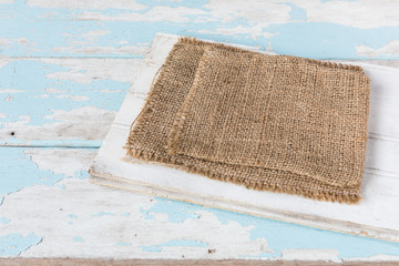 SACKCLOTH ON GRUNGE BLUE AND WHITE WOODEN BACKGROUND