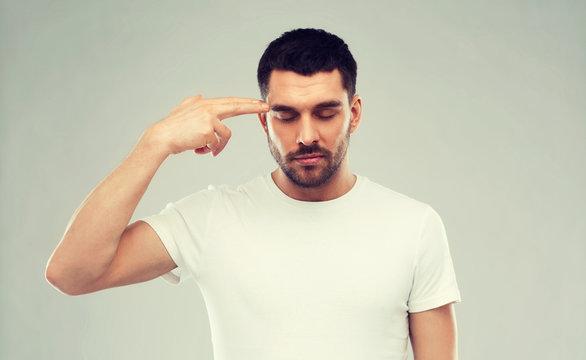 man making finger gun gesture over gray background