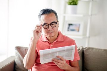 happy man in glasses reading newspaper at home