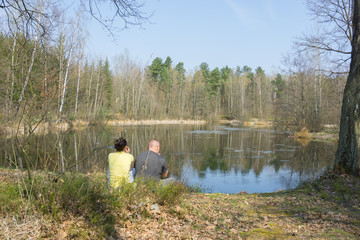 couple sits on the pond  in the spring forest