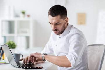businessman with laptop and wristwatch at office