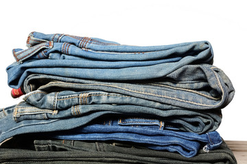 Stack of blue denim jeans on wooden table