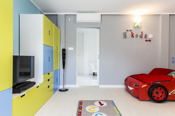 Little boy's room with a car shaped bed