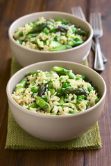 Green asparagus, pea, parsley and brown rice risotto served in bowls, photographed on dark wood with natural light (Selective Focus, Focus on the middle of the first dish)