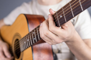 A picture of an acoustic guitar, classical color, in the hands of a guitarist