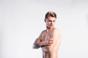 Young handsome hipster shirtless fitness man. Studio shot.