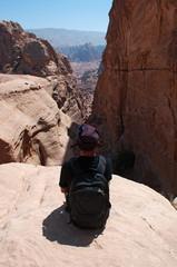 Giordania, 02/10/2013: un uomo di spalle seduto su una roccia sulla lunga salita, più di 800 gradini su un percorso a piedi, per arrivare al Monastero della città archeologica di Petra