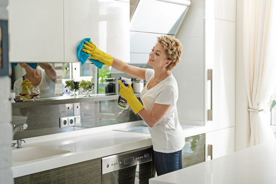 Active merry woman cleaning kitchen