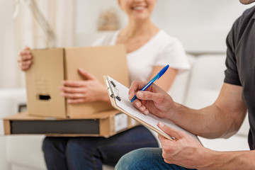 Deliveryman sitting on sofa near woman