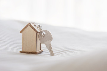 Symbol house with wood key on bed and sunlight, buy or rent estate concept.