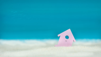 Symbol of little lilac house on the sand with bright blue painted sky background