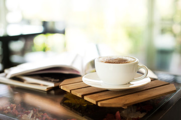 Cup of cappuccino with magazine on the table, coffee shop background, bright tone