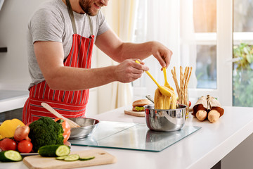 Man is satisfied with self-cooked pasta
