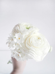 White wedding or birthday bouquet made of Persian buttercup, Ranunculus and daffodil, Narcissus, flowers. Blurred background.