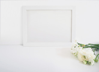 White blank wooden frame mockup with the Persian buttercup and daffodil flowers lying on the white table. Poster product design. Styled stock feminine photography. Home decor.
