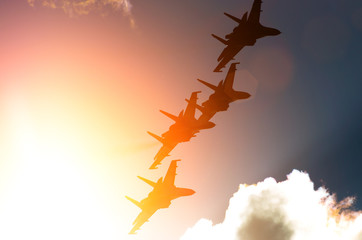 Aircraft fighter jets against the background of sky and sun