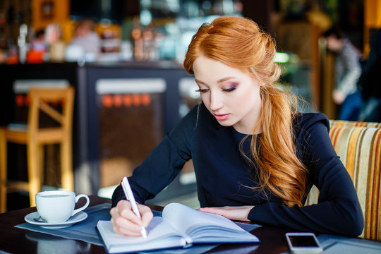 Confident young woman in smart casual wear concentrated on work while sitting in cafe