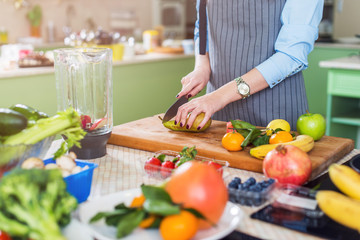 Cropped image of female cook cutting fruit on board preparing smoothie in kitchen